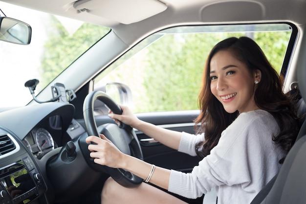 アジアの女性が車を運転し、喜んで前向きな表情で幸せに笑顔