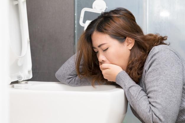 Азиатская женщина имеет утреннее недомогание