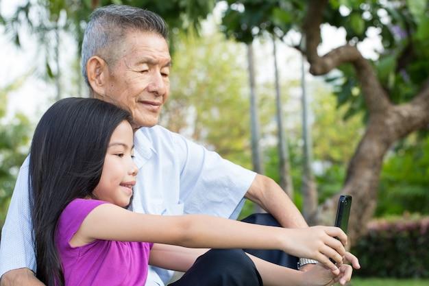 祖父と孫が公園でスマートフォンでセルフポートレートを作る
