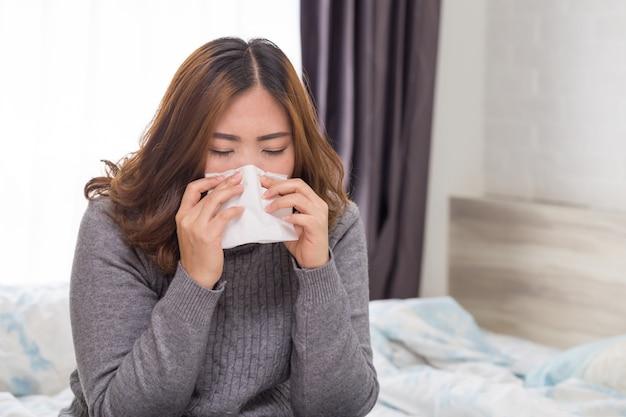 女性は風邪のためくしゃみをする