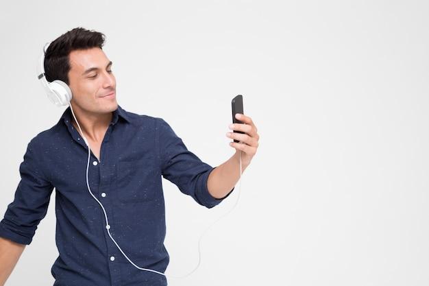 ハンサムな若い白人男がスマートフォンでヘッドフォンで音楽を聴く