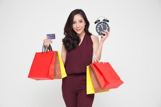 ミッドナイトセール、買い物袋と黒の目覚まし時計を保持している赤いドレスで幸せな若い女性の肖像画