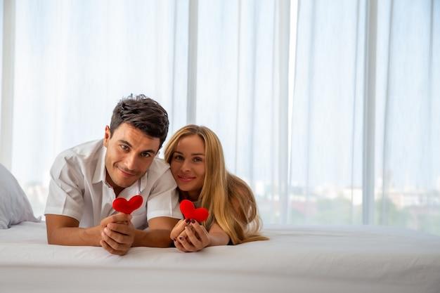 Пара улыбается и держит красное сердце на кровати
