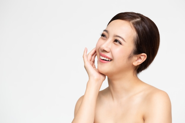 清潔で新鮮な肌の顔を持つ幸せな美しいアジア女性