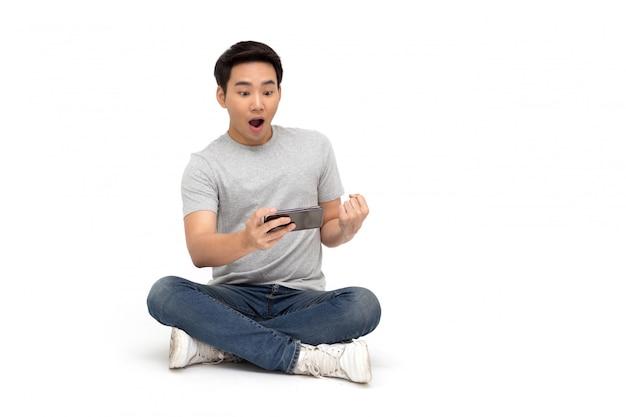 Молодое азиатское выражение вау человека и сидеть на поле пока использующ изолированный смартфон