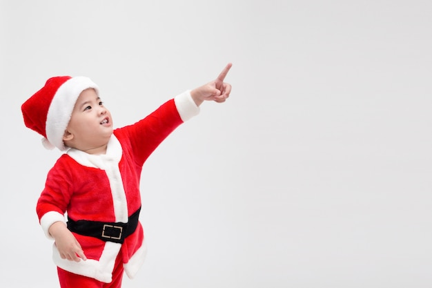 Азиатский мальчик в костюме рождества санта-клауса, указывая пальцами и смеясь, изолированных на белом, счастливой и улыбкой