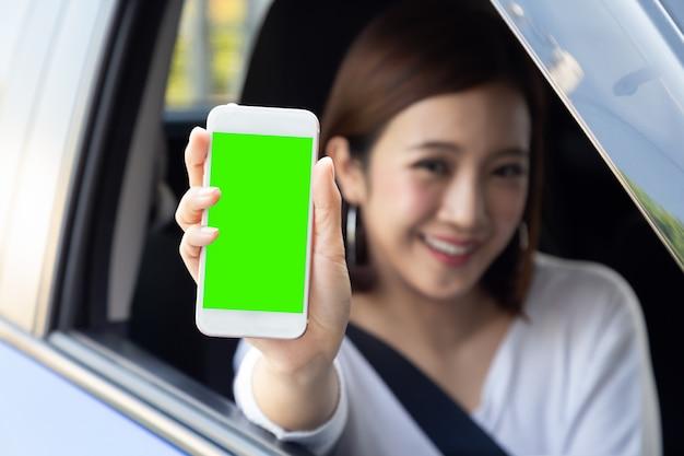 Азиатская женщина водитель сидит в машине и держит мобильный телефон с зеленым экраном