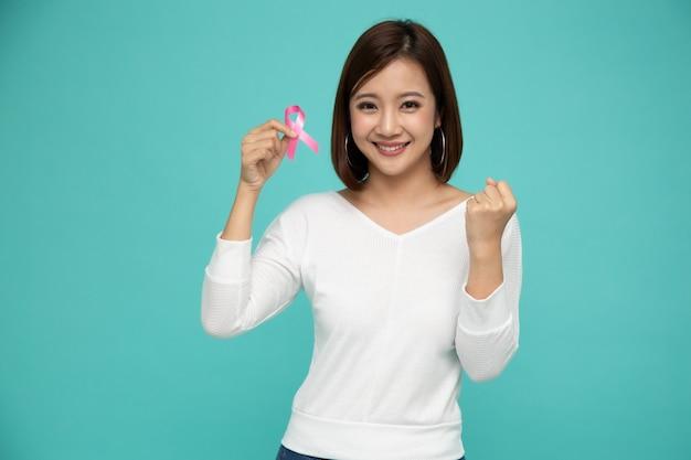 Молодая азиатская женщина держа розовую ленту рака бреста над изолированным салатовым