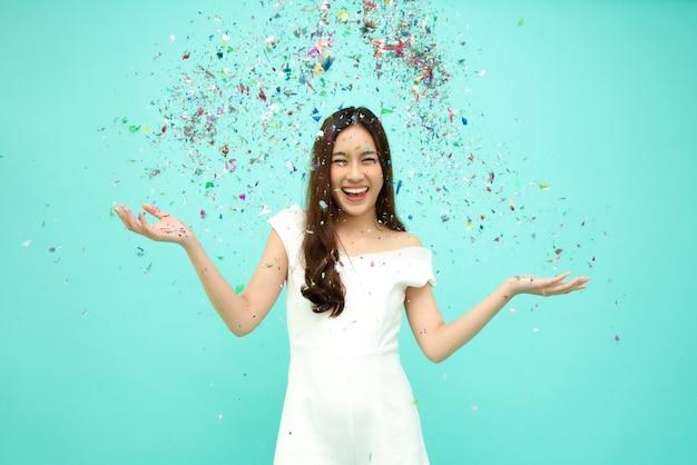 Веселая молодая азиатская женщина празднует с красочными конфетти