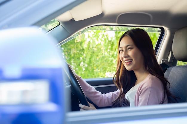 アジアの女性が車を運転し、旅行旅行へのドライブ中に喜んで肯定的な表現で幸せに笑顔
