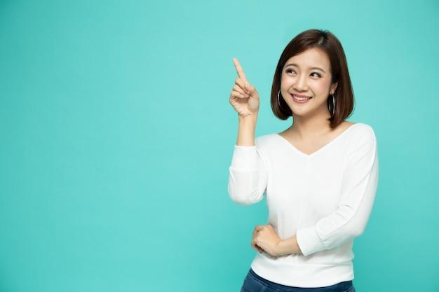Молодая элегантная азиатская женщина усмехаясь и указывая к пустому космосу экземпляра изолированному на зеленой стене