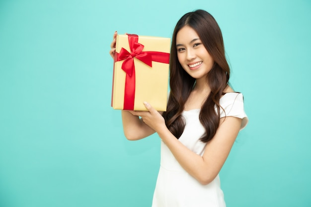 Счастливая красивая азиатская улыбка женщины при подарочная коробка золота изолированная на салатовой стене. девочки-подростки в любви, получая подарки