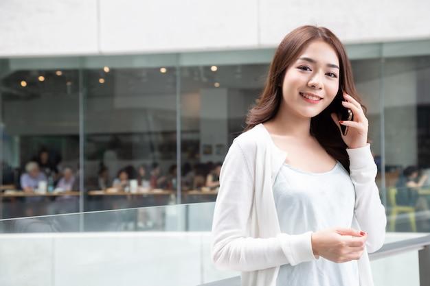 Молодая азиатская женщина вызывая на телефоне, говорить и беседе беседуя на черни с концепцией друга