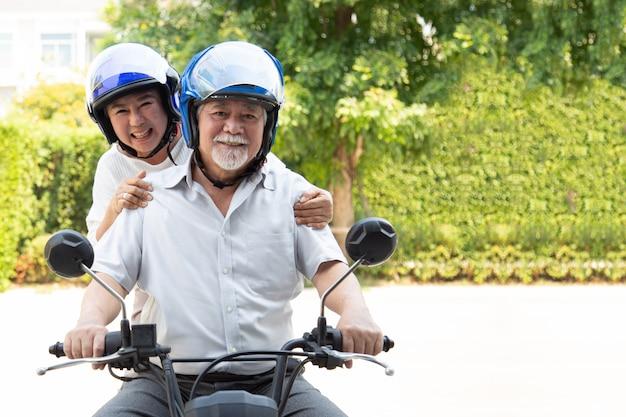 バイクに乗って上級アジアカップル、幸せなアクティブな老後、ライフスタイルのコンセプト