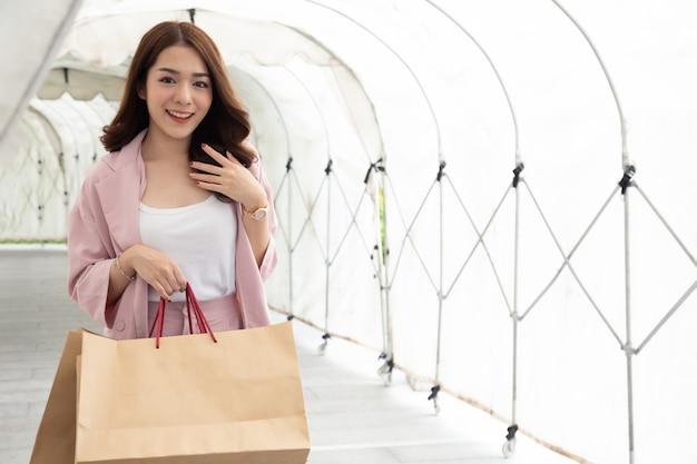 紙の買い物袋を押しながらトンネル、日焼け止めまたは防雨の中を歩く若いアジア女性