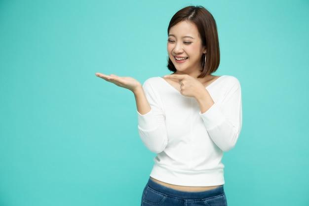 Молодая элегантная азиатская женщина усмехаясь и представляя для того чтобы опорожнить космос экземпляра изолированный на зеленой предпосылке, тайской модели