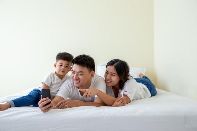 Счастливая молодая азиатская семья делает автопортрет с смартфон, отец, мать и сын маленький мальчик селфи на мобильном телефоне