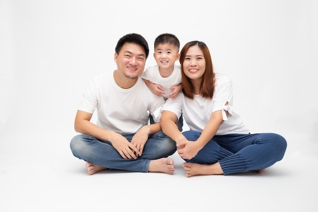 Азиатская семья усмехаясь и сидя совместно на поле изолировала белую стену. концепция молодой тайской семьи