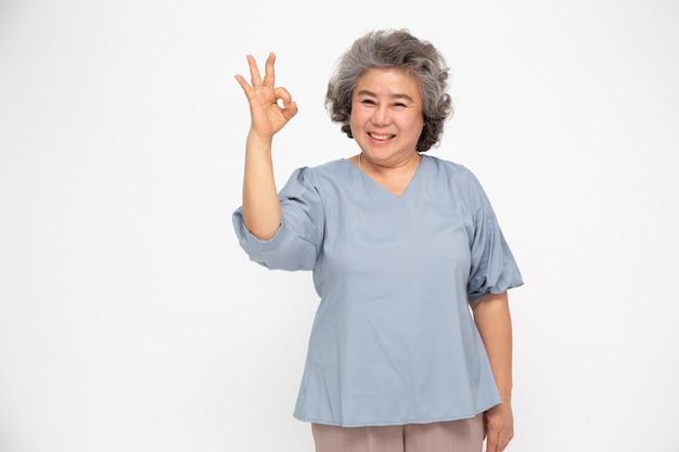 Портрет счастливого старшего азиатского жеста женщины или показ руки хорошо и смотря камеру изолированную на белой стене, более старая женщина чувствуя позитв и наслаждается концепцией