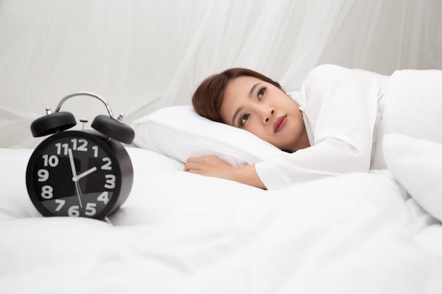 寝室の白いベッドに無力感と絶望感のあるアジアの女性、不眠症、うつ病の症状、警告標識のコンセプト