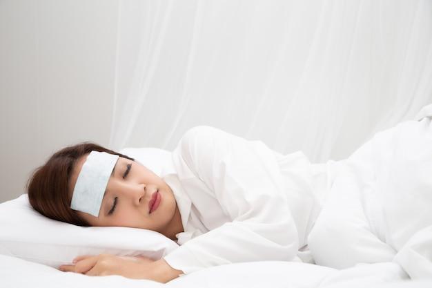 自宅の白いベッドで寝ている間に高熱を伴う若いアジアの女性、病気、発熱、咳、喉の痛みや感染症の細菌やウイルスによる病気など