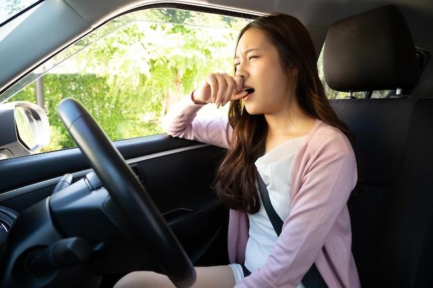 若いアジアの女性は車の中で汚れた悪臭のために彼女の鼻を保持します