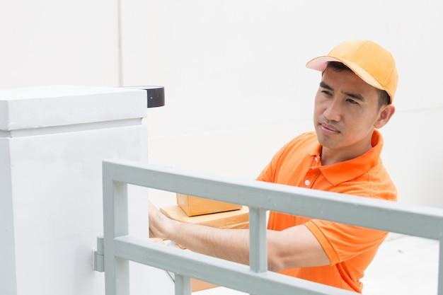 配達員がフロントホームで小包を受け取るために顧客を呼び出すためにベルを鳴らす
