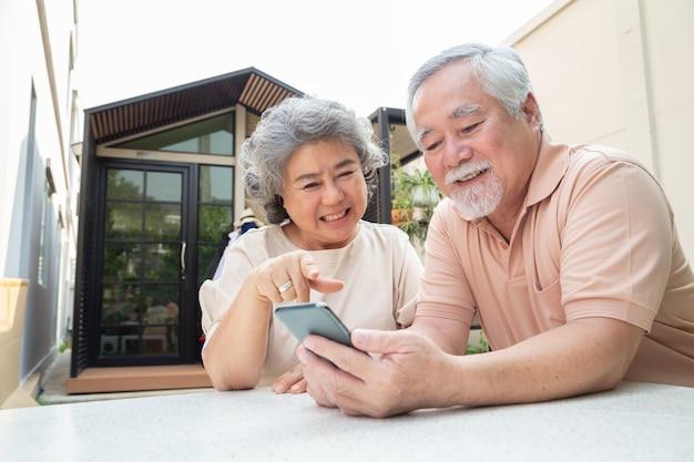 Азиатская пара старших говорить в чате видеозвонка на мобильный телефон, интеллектуальные технологии для старости и онлайн-активизм, оставаясь на связи концепции