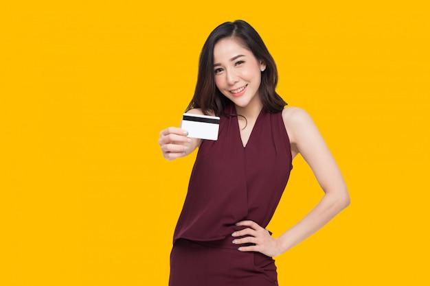 若い美しいアジアの女性の笑顔、表示、支払いまたはオンラインビジネスを支払うためのクレジットカードの提示、商人に支払う、または商品、カード所有者、またはカードを所有する人の前払いとして