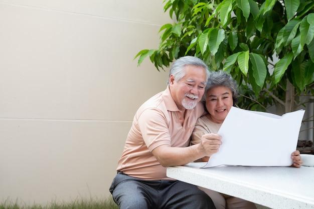 Счастливые азиатские старшие зрелые пары читая газету или кассету на переднем доме сада