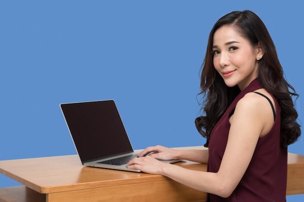 Молодая коммерсантка сидя и используя портативный компьютер изолированный над голубой стеной