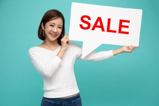 Счастливая азиатская женщина держа пузыри речи с красной продажей подписывает внутри руку изолированную на салатовой стене