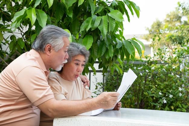 Взволнованная азиатская старшая пара чувствует себя пораженной