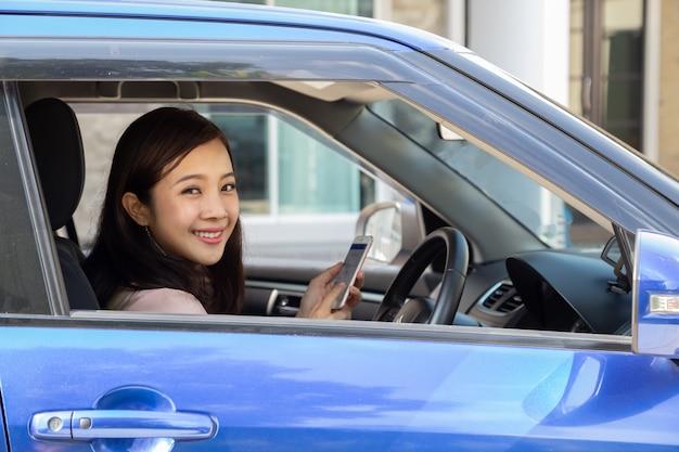 Азиатская женщина, используя смартфон в машине на дороге
