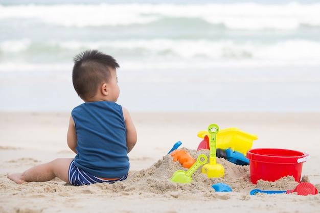 Первый летний мальчик играет с песком, принимая ребенка на пляж концепции