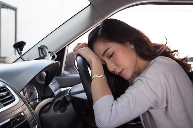 疲れ若い女性が車の中で眠る