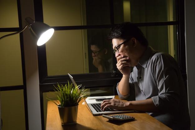 Бизнесмен сидит за ноутбуком в темном офисе, работает поздно концепции
