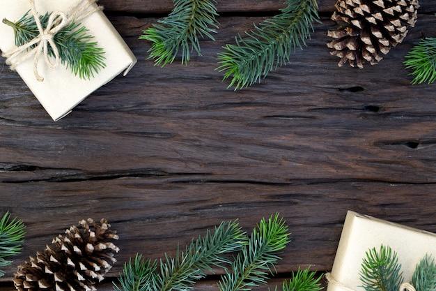クリスマスと新年あけましておめでとうございます組成、ギフトボックス、松ぼっくり、木製のモミの枝の平面図とテキストのコピースペース