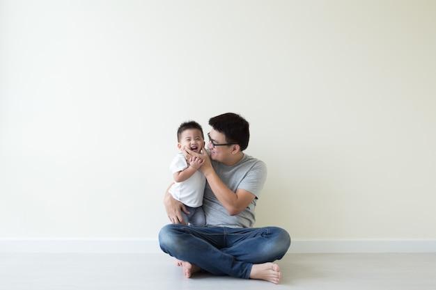 アジアの父と息子が遊んで、部屋の床に笑顔