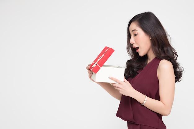 アジアの女性が赤いギフトボックスを開いて驚いた。