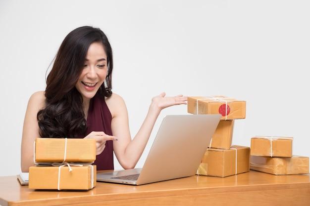 顧客と会話しているテーブルに宅配ボックスを持つアジアの女性。