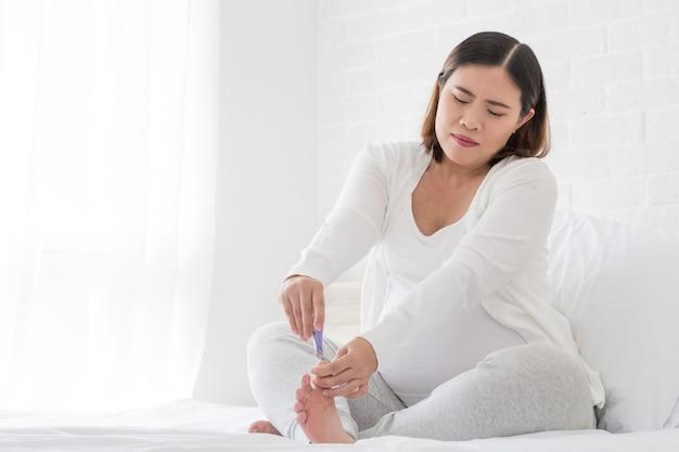 妊娠中の女性は寝室の白いベッドの上の爪切りで爪の足を切る