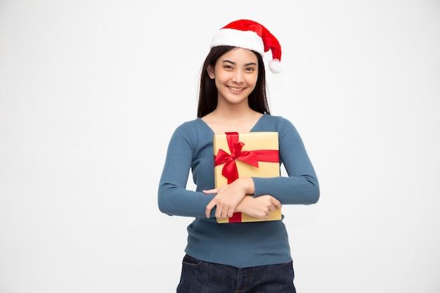 Счастливая азиатская женщина держа коробку подарка золота и нося шляпу санты.