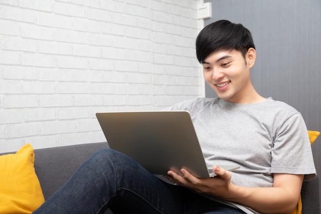 若いアジア人は彼のラップトップでブラウジングし、ソファーに座っています。