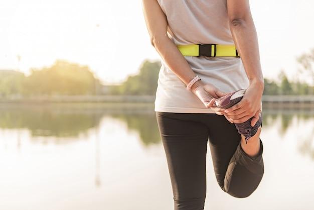 Молодой фитнес женщина бегун протягивать ноги перед запуском по городу