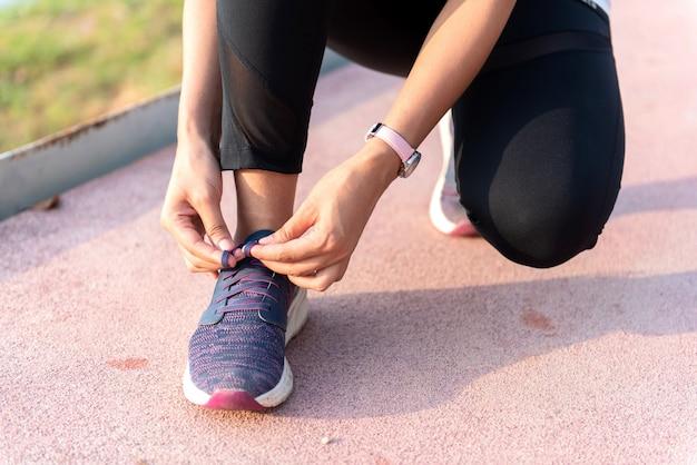 Молодая женщина бегун завязывает шнурки