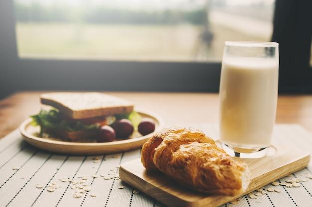 自家製サンドイッチ、オレンジジュース、木製テーブル