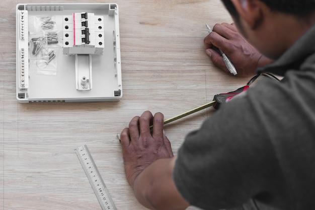 技術者が配電盤に回路ブレーカーを設計し設置する