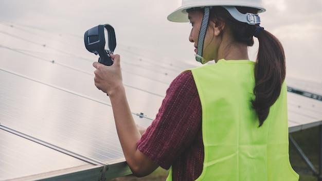 サーマルイメージャを使用して太陽電池パネルの温度熱をチェックする女性エンジニア