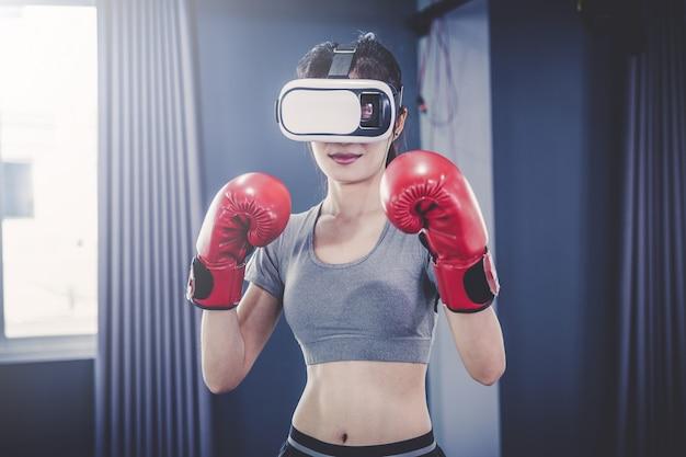 ボクシングやバーチャルリアリティを用いたフットワークの練習をしている若者が、ワークアウトクラスでゴーグルします。